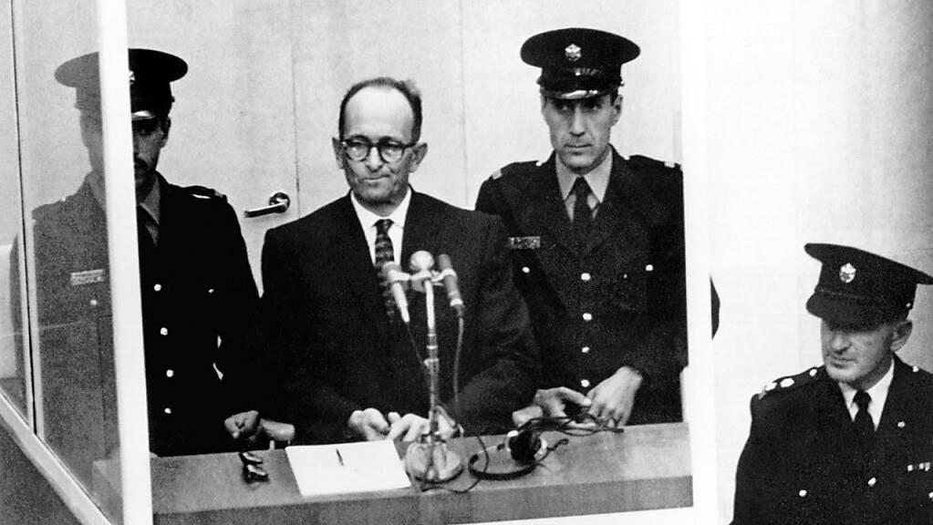 NS-Kriegsverbrecher Adolf Eichmann (2.v.l) steht während seiner Vernehmung am ersten Prozesstag vor dem Bezirksgericht in Jerusalem. Foto: picture alliance / dpa