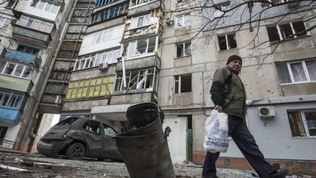 Ein Mann vor einem beschädigten Wohnblock in Mariupol