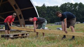 Die OK-Mitglieder David Meier, Lukas Renckly und Christian Döbeli (von links)stemmen die Balken für den Aufbau der Bühne. Nora Güdemann