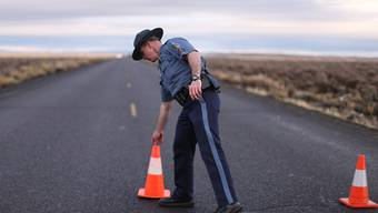 Ein Polizist im US-Bundesstaat Oregon installiert eine Strassensperre beim Naturpark, der von einer Bürgerwehr besetzt wurde.