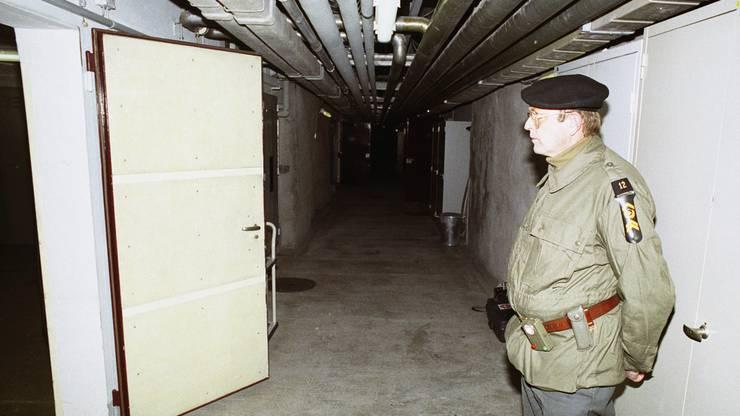 in Unteroffizier steht anlässlich einer Presseführung zur Information über die Geheimarmee P-26 in einem Durchgang der unterirdischen Bunkeranlage bei Gstaad im Berner Oberland, aufgenommen am 7. Dezember 1990. Der Stützpunkt diente der Geheimorganisation als Waffenlager und Ausbildungsanlage.  Im Bunker Schweizerhof ob Gstaad wurden Neuankömmlinge mit einer Videobotschaft des Generalstabschef begrüsst. Sie sprachen andere anwesende P-26-Mitglieder nur mit dem Tarnnamen an. Die richtigen Namen kannten sie nicht. Um sich gegenseitig nicht zu erkennen, trugen die Mitglieder im Bunker Kopfpariser.