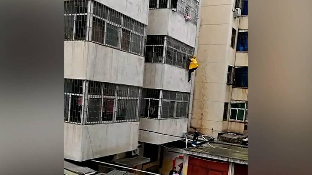 Kind baumelt von Fensterbrett: Mann klettert an Fassade in den dritten Stock