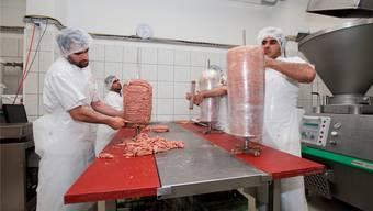 Die Mitarbeiter schichten die Fleischtürme in unglaublicher Geschwindigkeit aufeinander. Dann werden die Spiesse in Form geschnitten und in Folie gewickelt.Fotos: Emanuel Freudiger