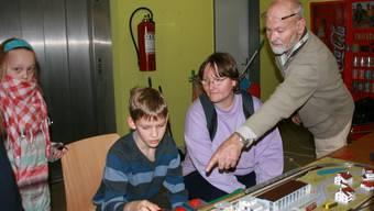 Massstab 1:220. Heinz Trachsel (stehend) erklärt, wie die Modelleisenbahn funktioniert.  fotos: barbara vogt