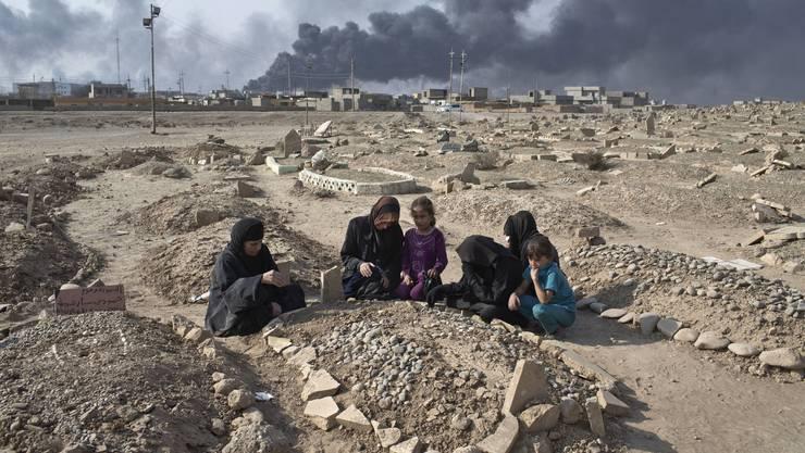 Eine Familie trauert an einem Friedhof, der von der IS beschädigt wurde.