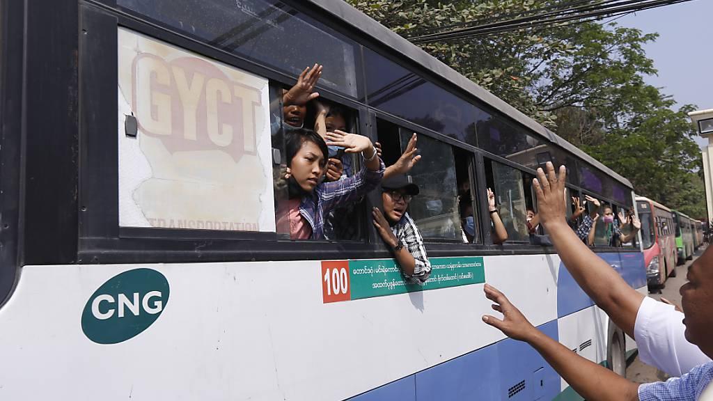 Festgenommene Demonstranten winken Menschen, während sie in einem Bus sitzen, der aus dem Insein-Gefängnis kommt und sie zu einem ungenannten Ort transportieren wird. Foto: Uncredited/AP/dpa