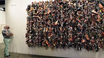 """Ein potenzieller Käufer begutachtet """"Ladies and Gentleman"""" von Hassan Sharif auf der Art Basel in Miami."""