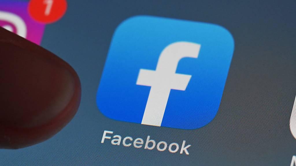 Eine Person zeigt auf einem Tablet auf die Facebook-App.