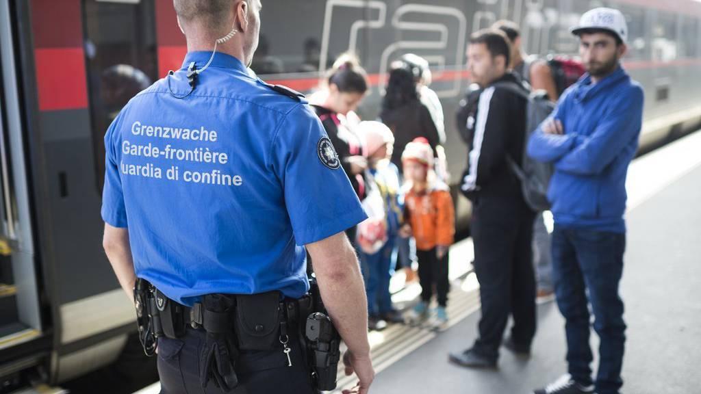 Ein Grenzwächter steht vor Fluechtlingen vor einem Railjet aus Wien, aufgenommen am Freitag, 25. September 2015, am Bahnhof in Buchs. (KEYSTONE/Gian Ehrenzeller)