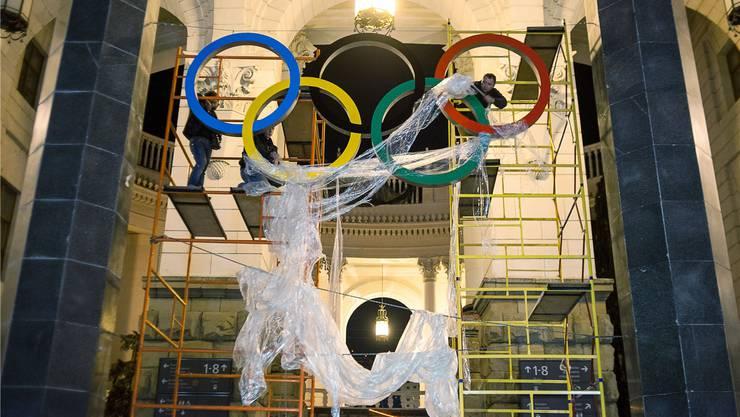 Arbeiter befestigen über dem Eingang des neuen Bahnhofs in Sotschi die olympischen Ringe. (Archiv)