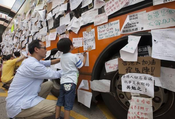 Vater und Sohn hinterlassen eine Nachricht am Demokratie-Bus