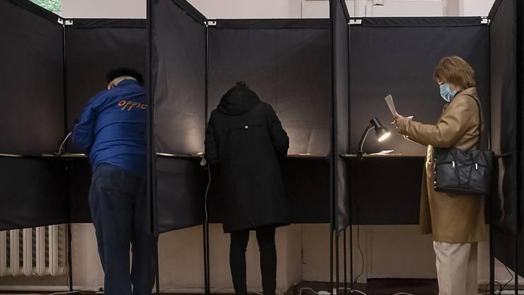 Wähler geben ihre Stimmen in Wahlkabinen ab. Foto: Mindaugas Kulbis/AP/dpa