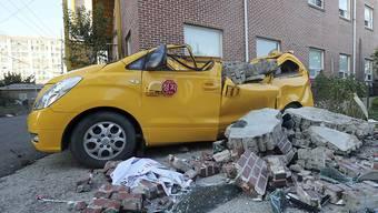 Dieses Auto wurde von einer wegen des Erdbebens eingestürzten Mauer beschädigt.