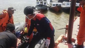 Rettungskräfte bergen eines der Opfer des Bootsunglücks zwischen Malaysia und Indonesien. Die Unfallursache ist noch ungeklärt.