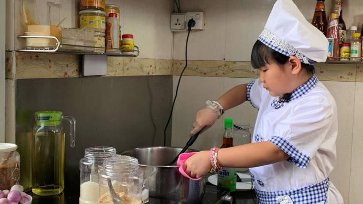 HANDOUT - Die achtjährige Moe Myint May Thu beim Kochen in ihrer Küche. Sie ist während des Lockdowns in Myanmar zu einer kleinen Starköchin geworden. Foto: --/privat/dpa - ACHTUNG: Nur zur redaktionellen Verwendung im Zusammenhang mit der aktuellen Berichterstattung und nur mit vollständiger Nennung des vorstehenden Credits