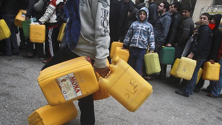 Menschen im Gaza-Streifen stehen Schlange, um Treibstoff-Behälter zu füllen. (Archiv)
