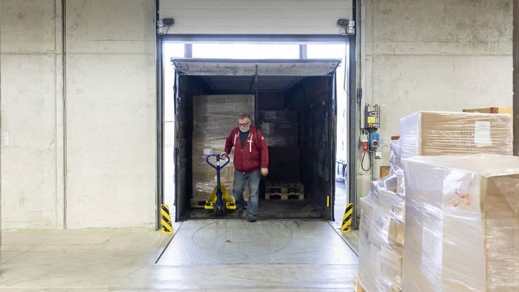 Spediteure bringen die Waren ins Lager und laden sie bei der Annahme ab.