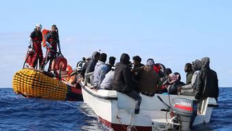 Seenotretter nähern sich einem Boot mit 30 Migranten auf dem Mittelmeer vor der Küste Libyens. (Archivbild)