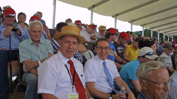 Regierungsrat Urs Hofmann (mit blauer Krawatte) und OK-Präsident Ueli Küng (mit Strohhut) verfolgen das Fest inmitten der Schwingerfans von der Tribüne aus.
