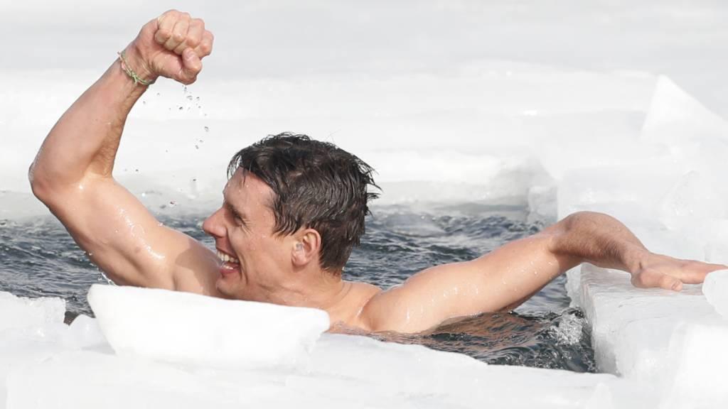 David Vencl freut sich und streckt die Faust nach oben während er in einem Loch im Eis in einem zugefrorenen See schwimmt. Foto: Petr David Josek/AP/dpa