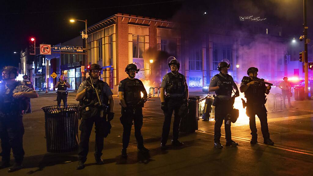 Die Polizei in Minneapolis steht Wache, nachdem Demonstranten nach einer Mahnwache für Winston Boogie Smith Jr. Müllcontainer auf der Straße in Brand gesetzt haben. Smith wurde am 03.06.2021 während einer Haftbefehlsaktion von Polizeibeamten erschossen. Foto: Christian Monterrosa/AP/dpa