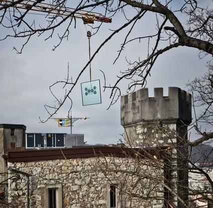 Mit einem Kran wird ein 2,5 auf 2,5 Meter messendes Fensterelement über das Schloss gehoben.