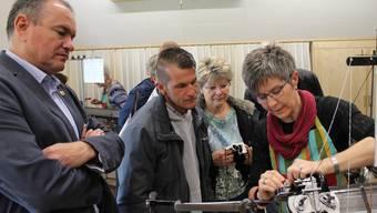 Stadtammann Herbert Weiss (l.) und Besucher lasen sich erklären, wie die Strickmaschine funktioniert.