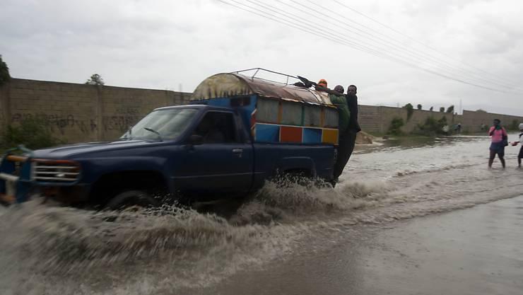 Ein Auto fährt durch eine überflutete Strasse in Port-au-Prince, der Hauptstadt von Haiti.
