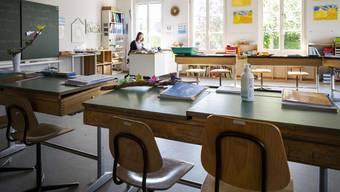 Eine Primarlehrerin allein im Klassenzimmer.