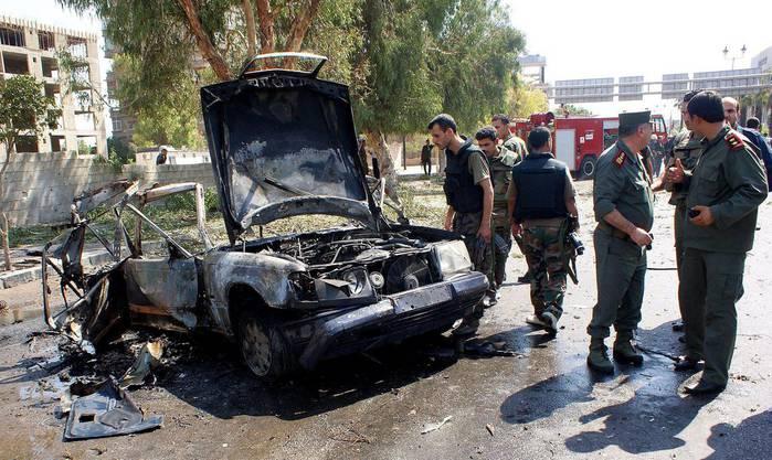 Syrische Polizisten untersuchen eine detonierte Autobombe