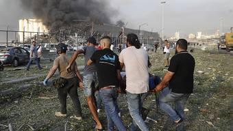 Helfer tragen nach einer schweren Explosion in Beirut ein Opfer, während im Hintergrund Rauch aufsteigt. Foto: Hussein Malla/AP/dpa