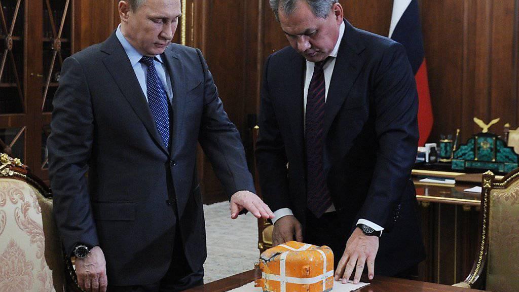 Russlands Präsident Wladimir Putin und Verteidigungsminister Sergei Schoigu präsentieren den Flugschreiber des abgeschossenen Kampfjets.
