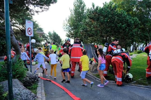Die Kinder bahnen sich ihren Weg an den Feuerwehrleuten vorbei...