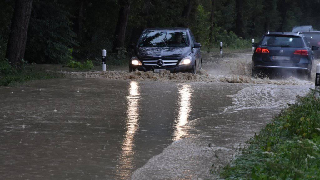 Der Dauerregen hat dem Verkehr in der Ostschweiz zugesetzt: Autofahrer unterwegs auf einer überschwemmten Strasse zwischen Diepoldsau und Berneck.