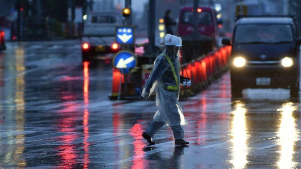 Ein Mann überquert bei Regen und starkem Wind eine Strasse in Tokio. Auch im Raum der japanischen Hauptstadt schwollen wegen Taifun «Lan» Flüsse an.