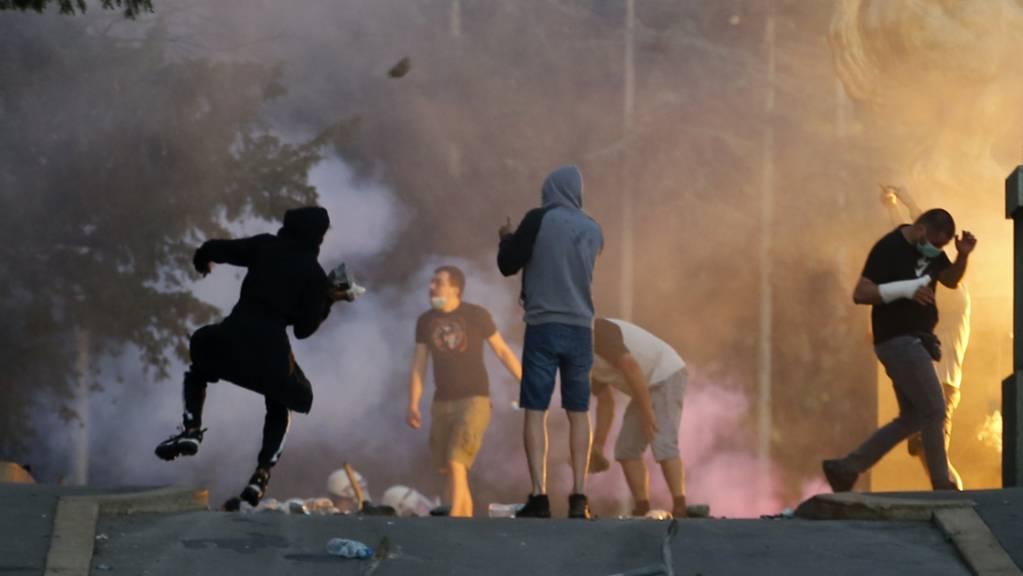 dpatopbilder - Demonstranten stoßen bei Protesten mit Polizisten zusammen. Nach massiven Protesten in der Nacht zum Mittwoch hat Serbiens Präsident Vucic eine von ihm angekündigte Ausgangssperre wegen der Corona-Pandemie zurückgenommen. Foto: Darko Vojinovic/AP/dpa