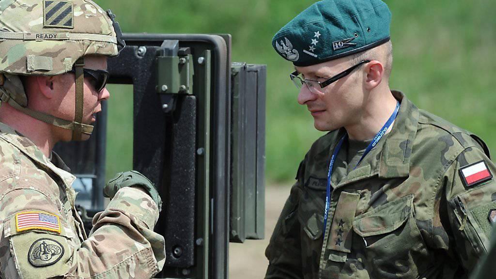 Ein US-Soldat im Gespräch mit seinem polnischen Kollegen (rechts) während einer Übung im Nordwesten Polens.
