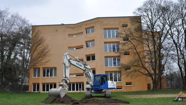Hier kommt das neue Schulhaus hin. Bei den grossen Fenstern rechts hinter dem Bagger wird das alte mit dem neuen Gebäude verbunden.