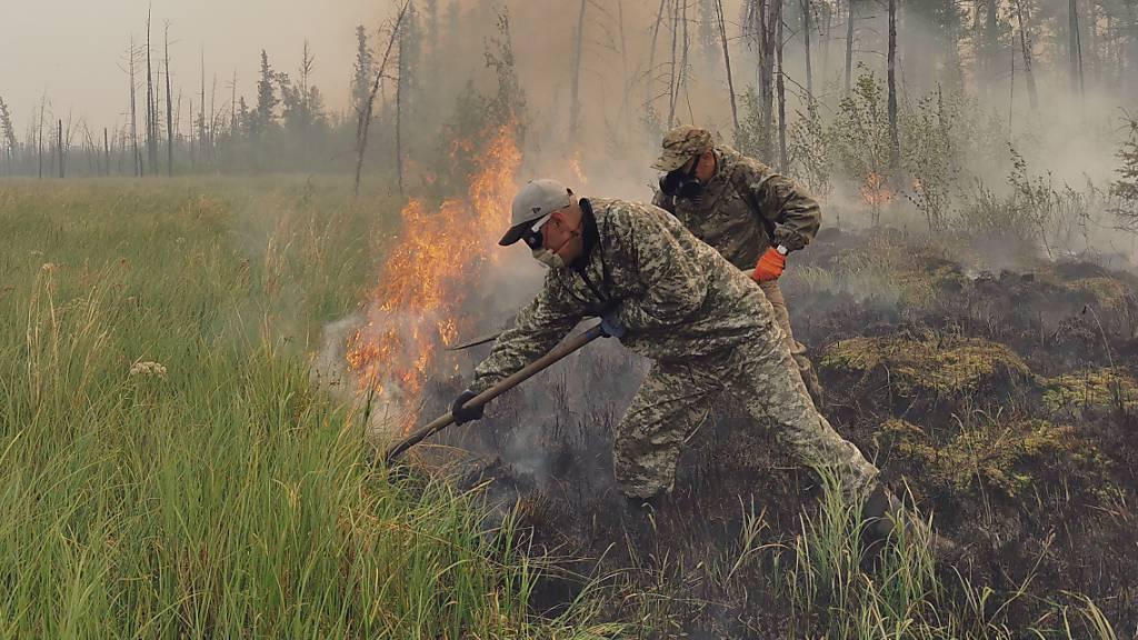 Freiwillige löschen einen Waldbrand in der Republik Sacha, auch bekannt als Jakutien, im Fernen Osten Russlands, Samstag, 17. Juli 2021. Foto: Ivan Nikiforov/AP/dpa