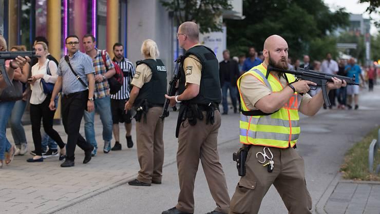 Menschen verlassen das Olympia-Einkaufszentrum in München nach dem tödlichen Anschlag - die Polizei ist in Stellung.