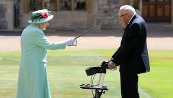 Königin Elizabeth II. schlägt Tom Moore, Weltkriegsveteran und Rekord-Spendensammler, während einer Zeremonie im Freien auf Schloss Windsor zum Ritter.