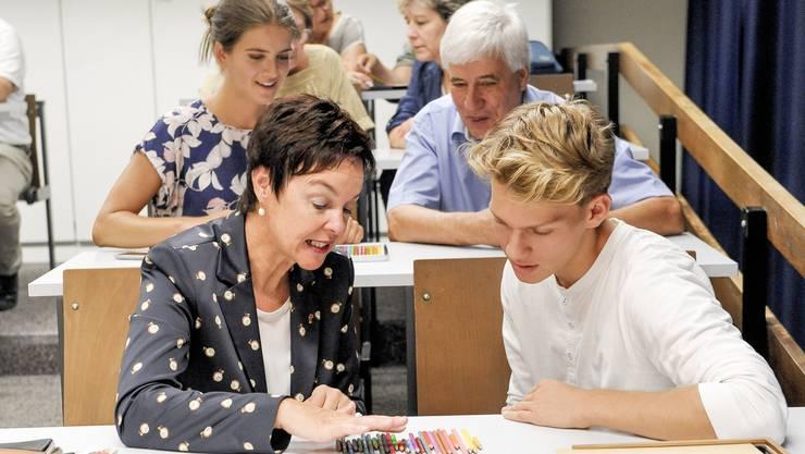 Regierungsrätin Monica Gschwind durfte sich am Gym Oberwil im Chemieunterricht versuchen. Es ist kein Leichtes, Farbstifte im Dämmerlicht der Regenbogen-Kaskade entsprechend zu ordnen.