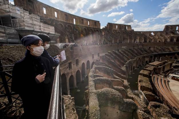 Touristen mit Maske im Kolosseum von Rom.