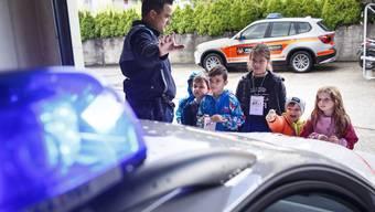 Kindergartenkinder aus Grenchen schauen sich Polizeiauto an