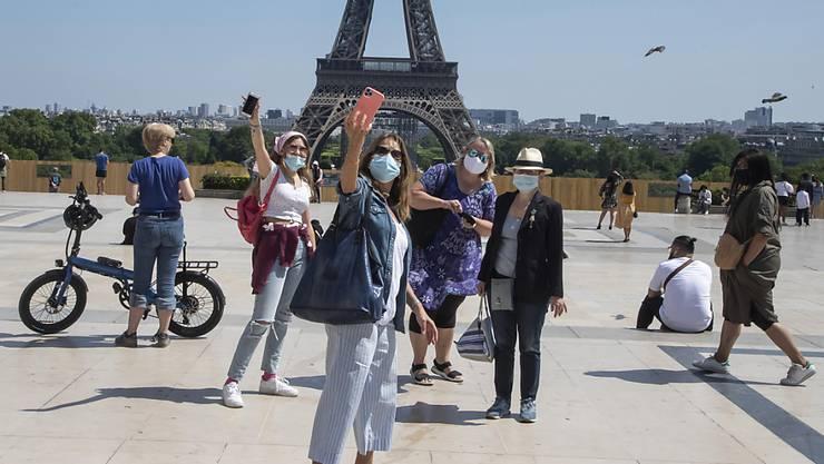 Menschen mit Mundschutzen machen Selfies vor dem Eiffelturm auf dem Trocadero-Platz. Die Pariser genießen ihr erstes Wochenende in der Sonne seit den teilweisen Lockerungen der Reise- und Bewegungsbeschränkungen. Foto: Michel Euler/AP/dpa