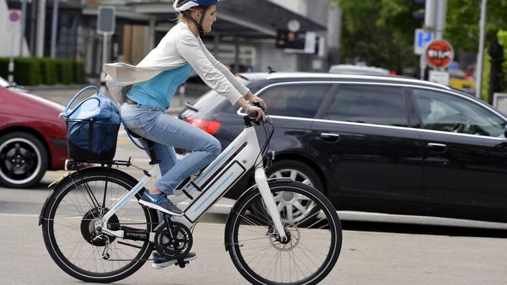 Prägen das Strassenbild immer mehr: Eine Elektrobike-Fahrerin fährt auf einer Strasse in Zürich.