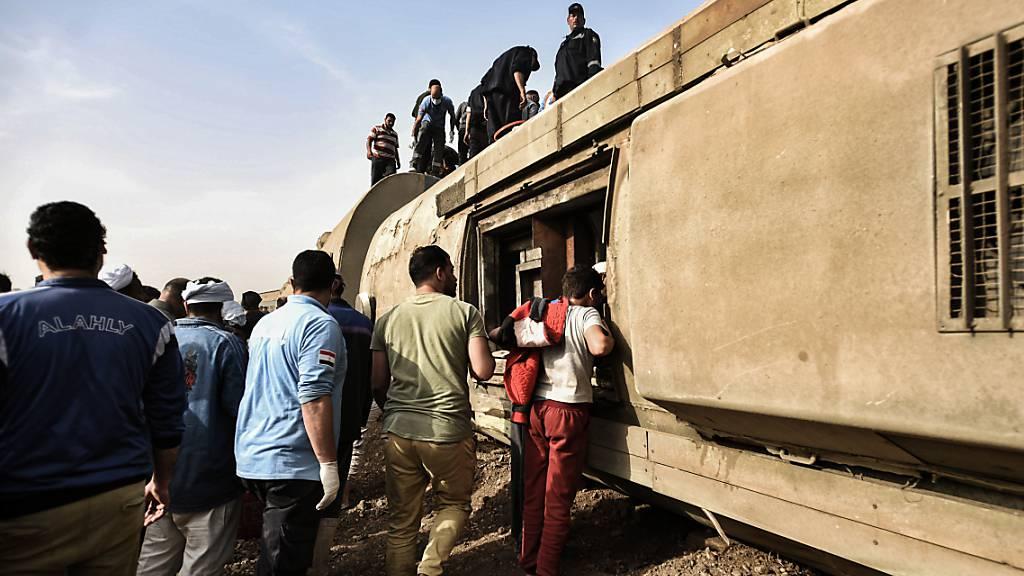 Menschen stehen vor und auf einem umgekippten Waggon eines Zugs. In Ägypten hat sich erneut ein schweres Zugunglück ereignet - diesmal mit rund 100 Verletzten. In der Provinz Kaljubia in der Nähe von Kairo seien acht Waggons entgleist, teilte der Gouverneur der Provinz bei Facebook mit. Foto: Sayed Hassan/dpa