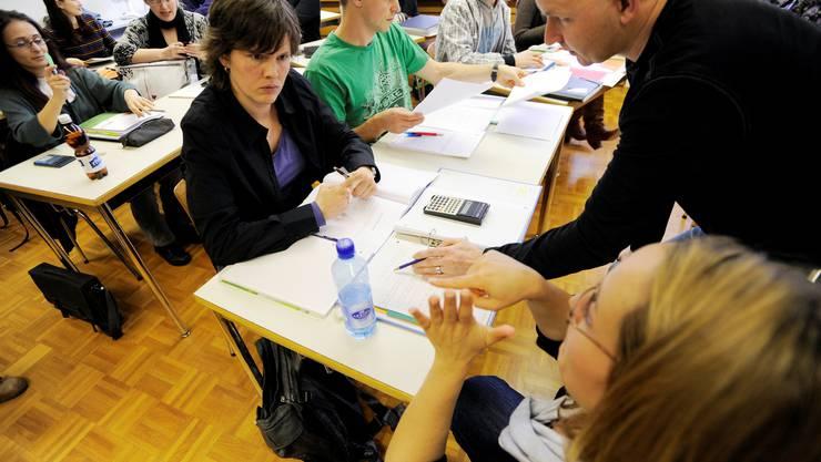 Eine Dolmetscherin übersetzt einer gehörlosen Schülerin die Erklärungen des Mathematiklehrers. Die Schülerin sitzt mit ihren drei gehörlosen Kollegen in der ersten Reihe.