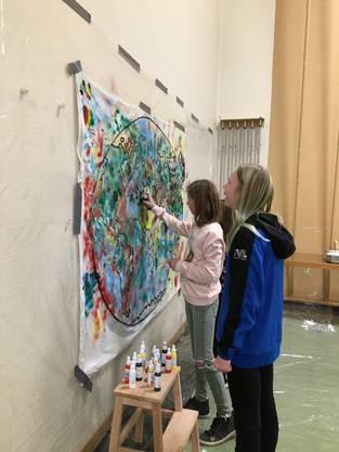 Jugendliche bemalen das Gemeinschaftsbild am Mädchenkulturtag