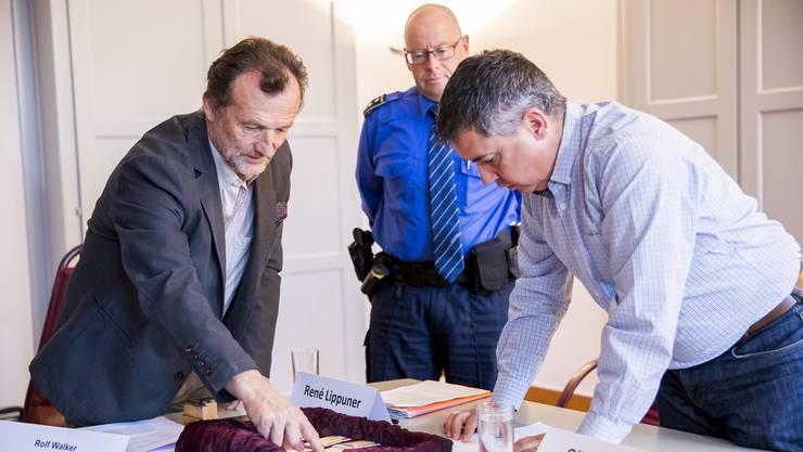 <p>Gemeindeschreiber Rolf Walker und Gemeindeammann Oliver Brun überprüfen die Goldbarren vor Polizeichef Zurzibiet Rene Lippuner.</p>